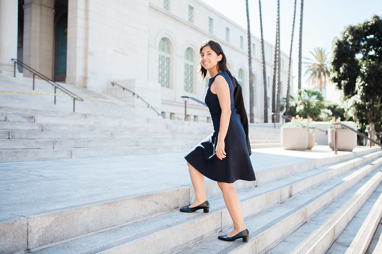 A young woman with shoulder-length brown hair walks up white stone stairs, wearing a black dress and black shoes.