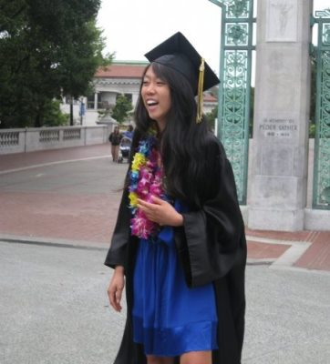 A young woman with long wavy black hair in a blue dress and black graduation gown, smiling outdoors.