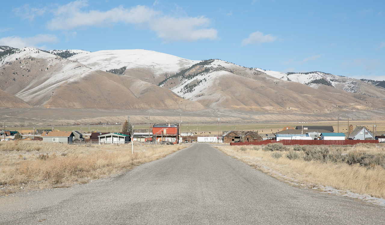 A long, open road in a small town with brown grass on either side; in the distance, wooden house and barn structures are visible and snow-capped mountains are in the background.