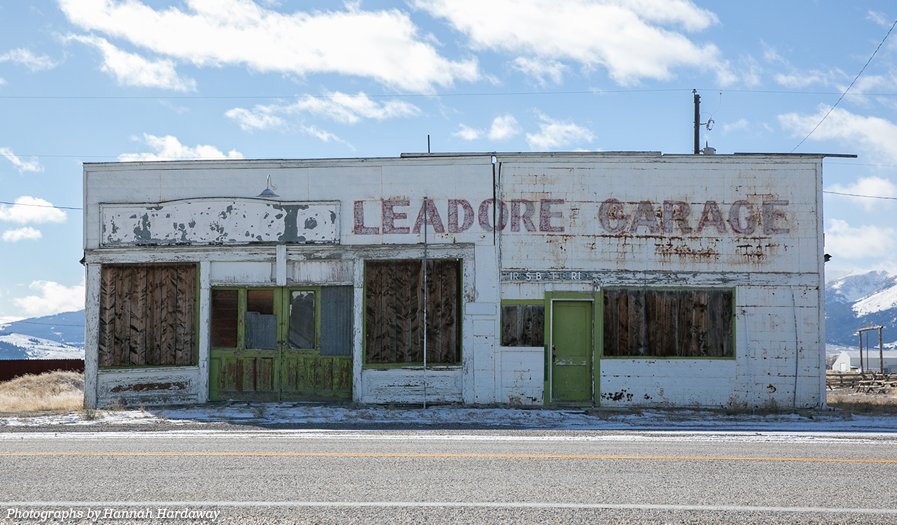 "An old, dilapidated brick building painted white with the windows boarded up that reads, ""Leadore Garage"" at the top; behind the building, snow-capped mountains are visible."