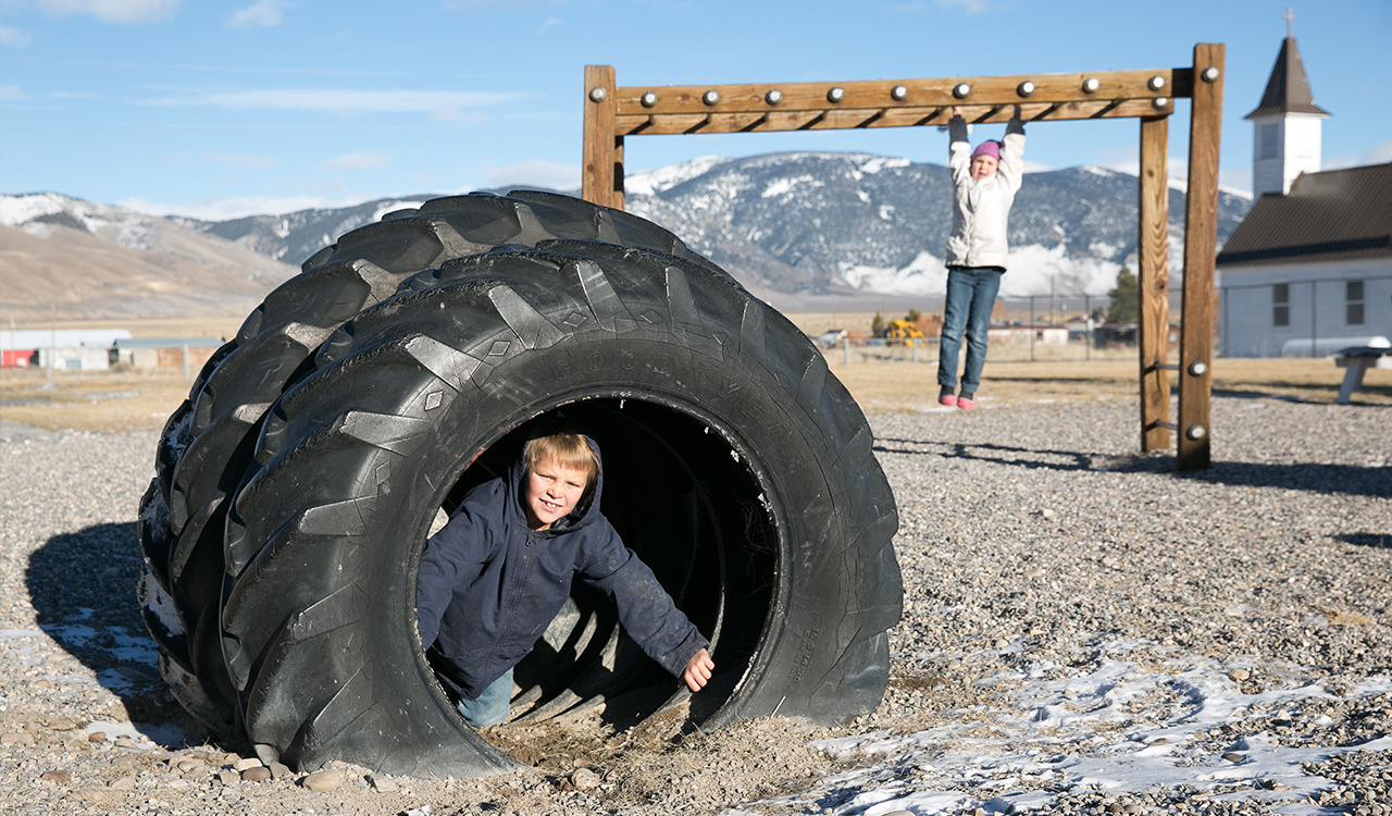Two students play on a snowy playground: one is inside of a large tire structure and one is hanging from monkey bars; in the background are several snow-capped mountains.