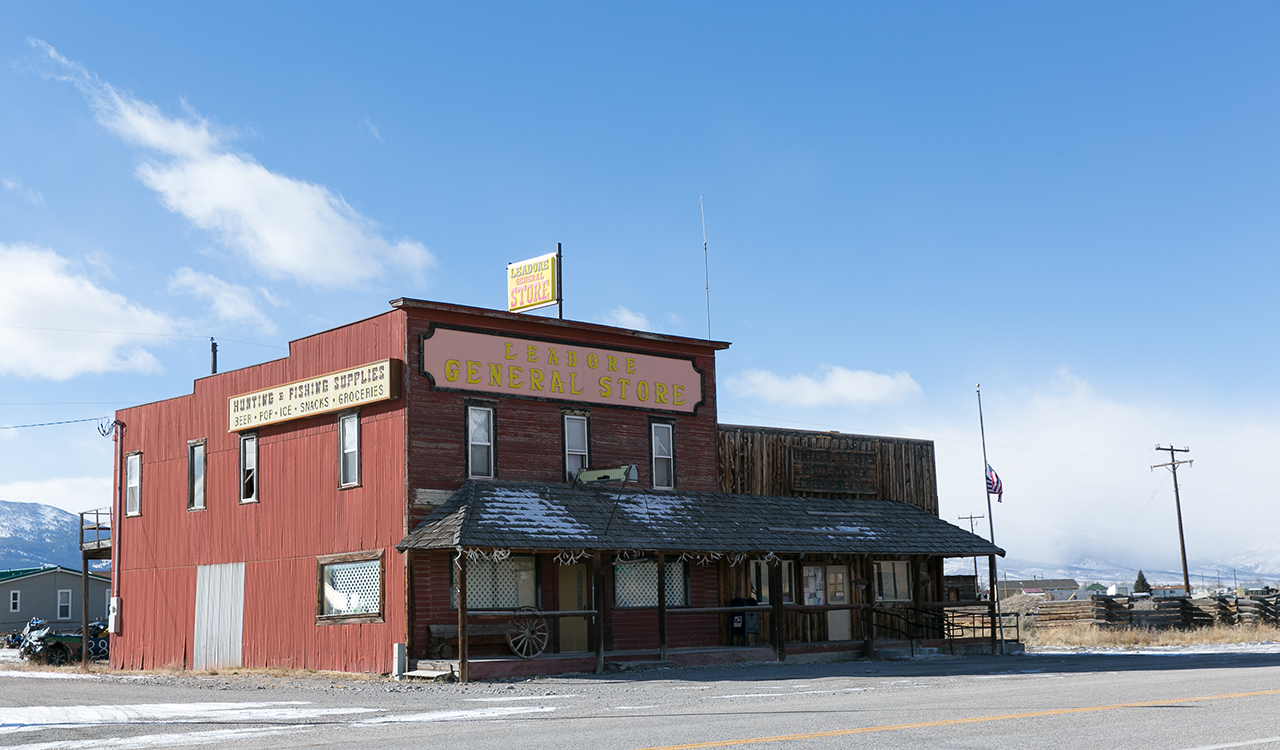 "A two-story wooden building at reads, ""Leodore General Store"" at the top; on the side, it reads, ""Hunting and Fishing Supplies; beer, pop, ice, snacks, groceries""; snow capped mountains are visible in the background."