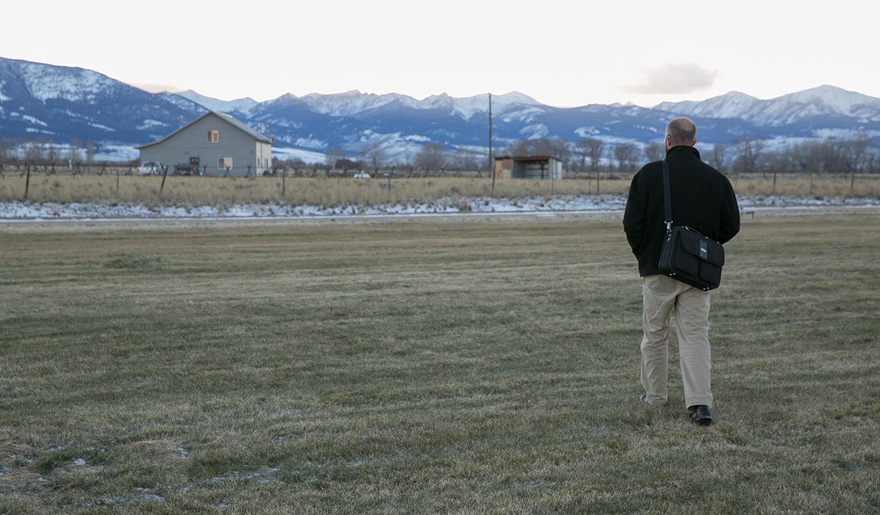 The back of a young adult male walking across a large grassy field towards a house, he wears a jacket and work bag; in the background are several snow-capped mountains.