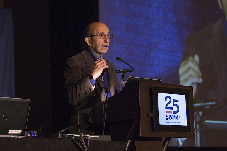 A middle-aged man in a gray suit speaks from a podium with the Teach for America logo.