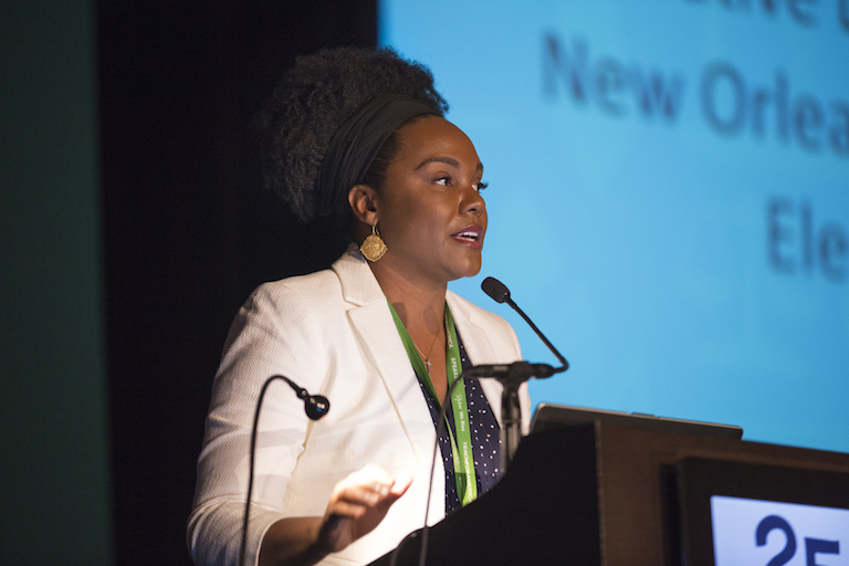 A woman with thick curly black hair in a white blazer speaks from a podium at the TFA 25th anniversary event.