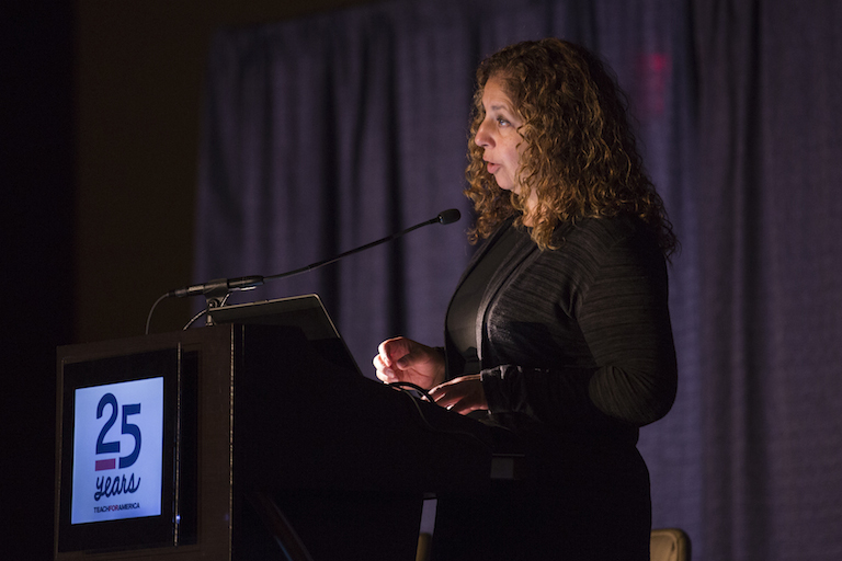 A woman with thick curly brown hair wearing a black sweater speaks from a podium at the TFA 25th anniversary event.