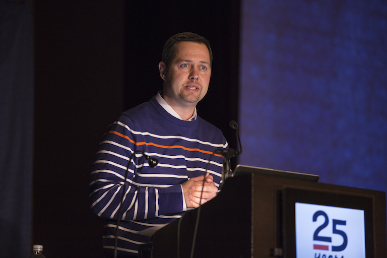 A man with short brown hair in a striped sweater speaks from a podium at the TFA 25th anniversary event.
