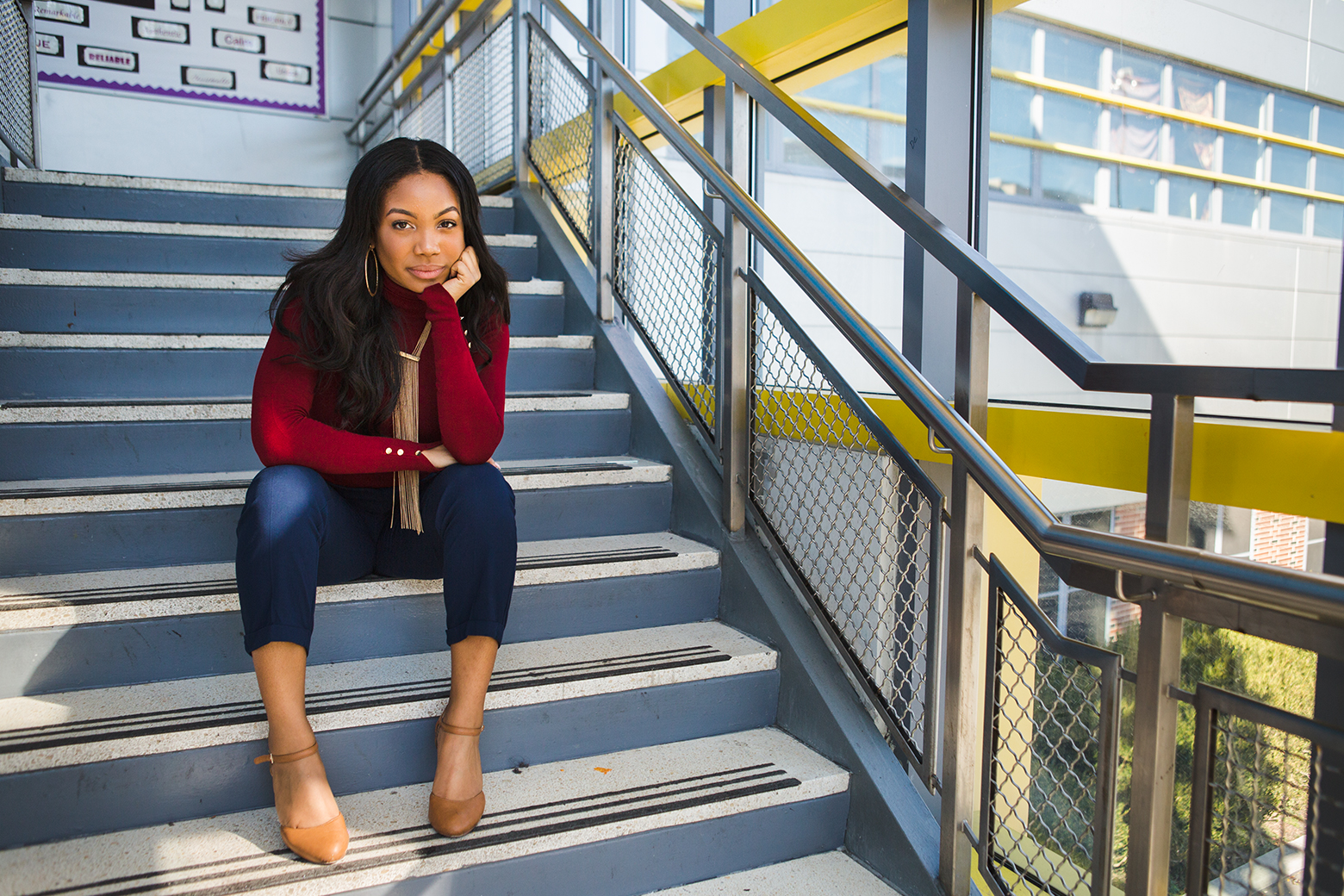 A young woman with long black hair wearing a red shirt, blue pants, and beige shoes sitting in a stairwell next to large windows looking out onto a building in the sun.