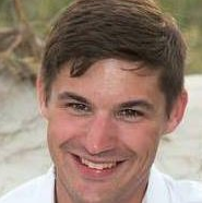 Close head shot of a young man with thick brown hair smiling on a beach.