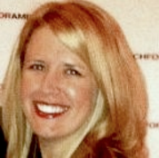 Head shot of a young woman with thick blonde hair smiling in front of a Teach for America  photo wall.