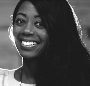 Black and white image of a smiling young woman with thick black hair, backlit.