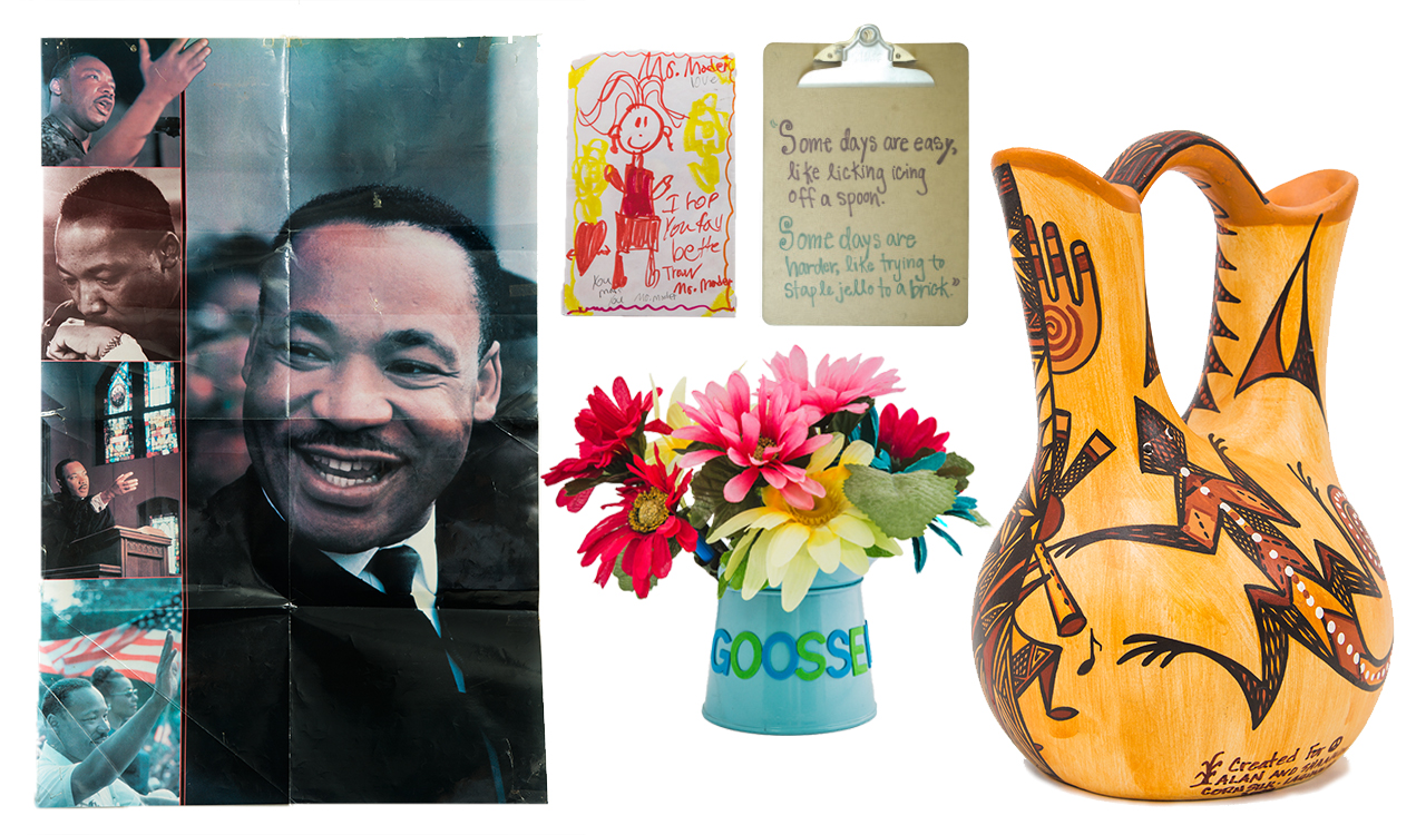 A collection of five items: an MLK poster collage, a student drawing of a person, a clip board, an African jug, and a blue watering can full of flowers.