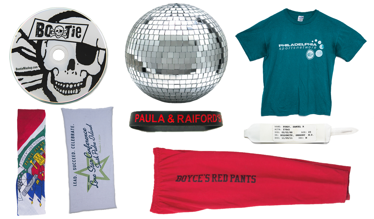 A collection of 8 artifacts: a Bootie CD, a disco ball, a Philadelphia Sports Network t-shirt, a hospital name bracelet, a Paula & Raifords bracelet, red sweatpants, two headbands.