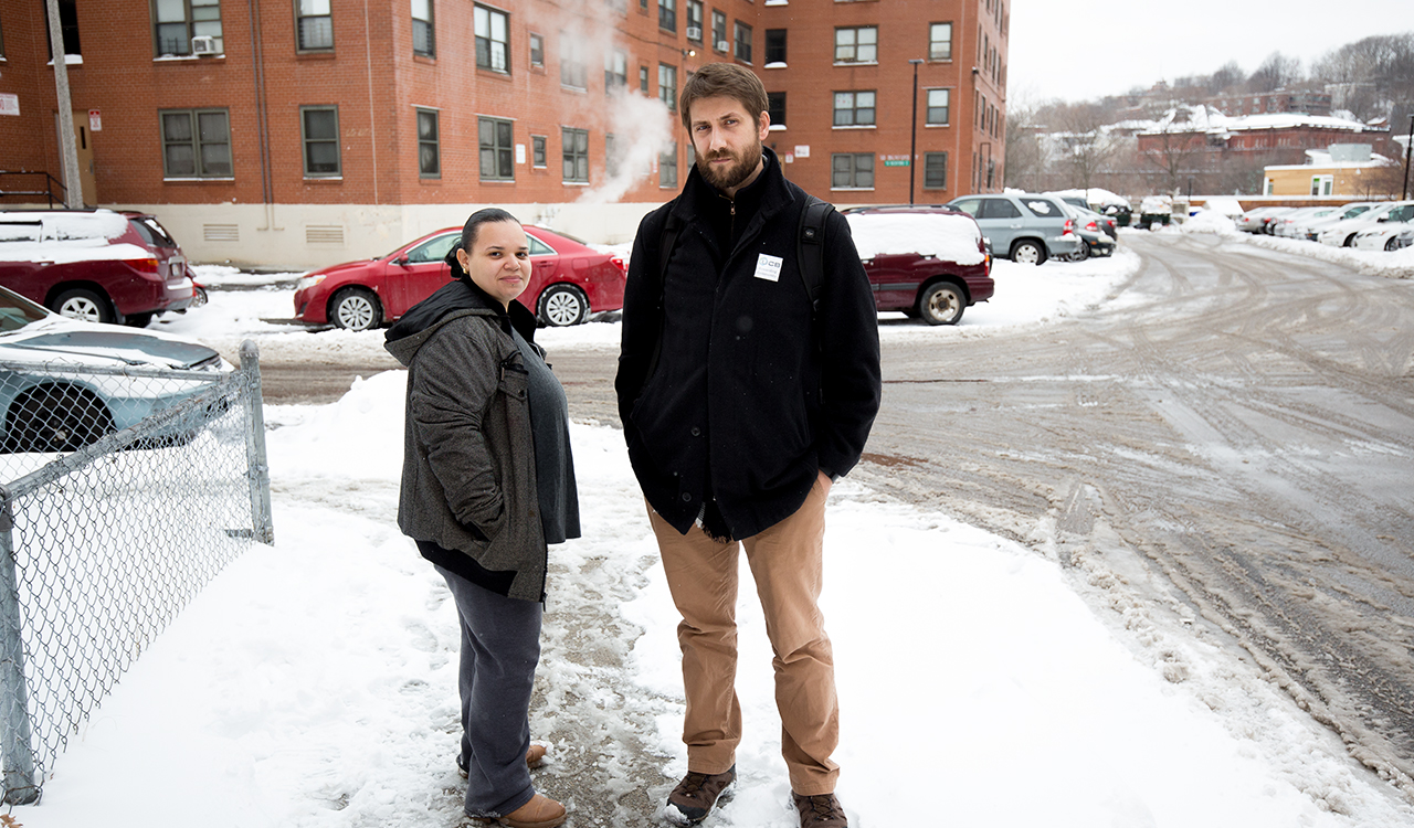 A tall man with a beard wearing a black coat and a shorter woman wearing a gray coat standing on a snowy sidewalk.