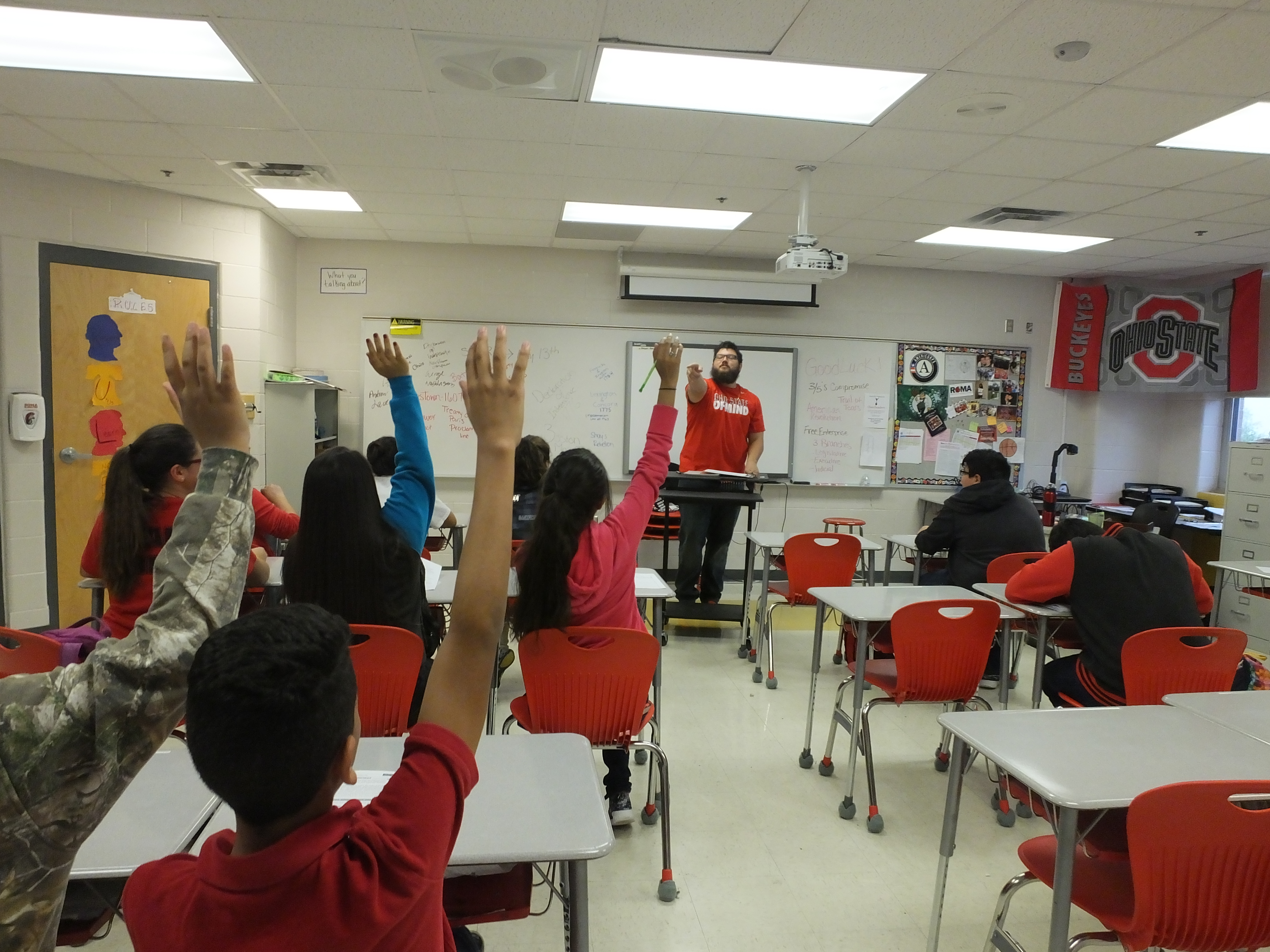 Teacher calling on students with raised hands in class
