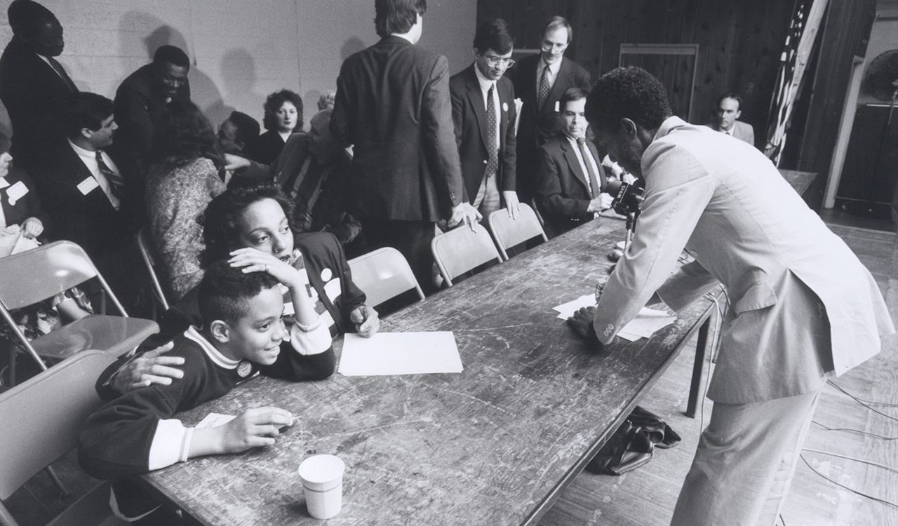 Black and white photo of a young boy and a woman sitting at a table, a man in a light colored suit bending over a table to look at his notes further down, and a group of men and women in suits sitting in the corner in the background.
