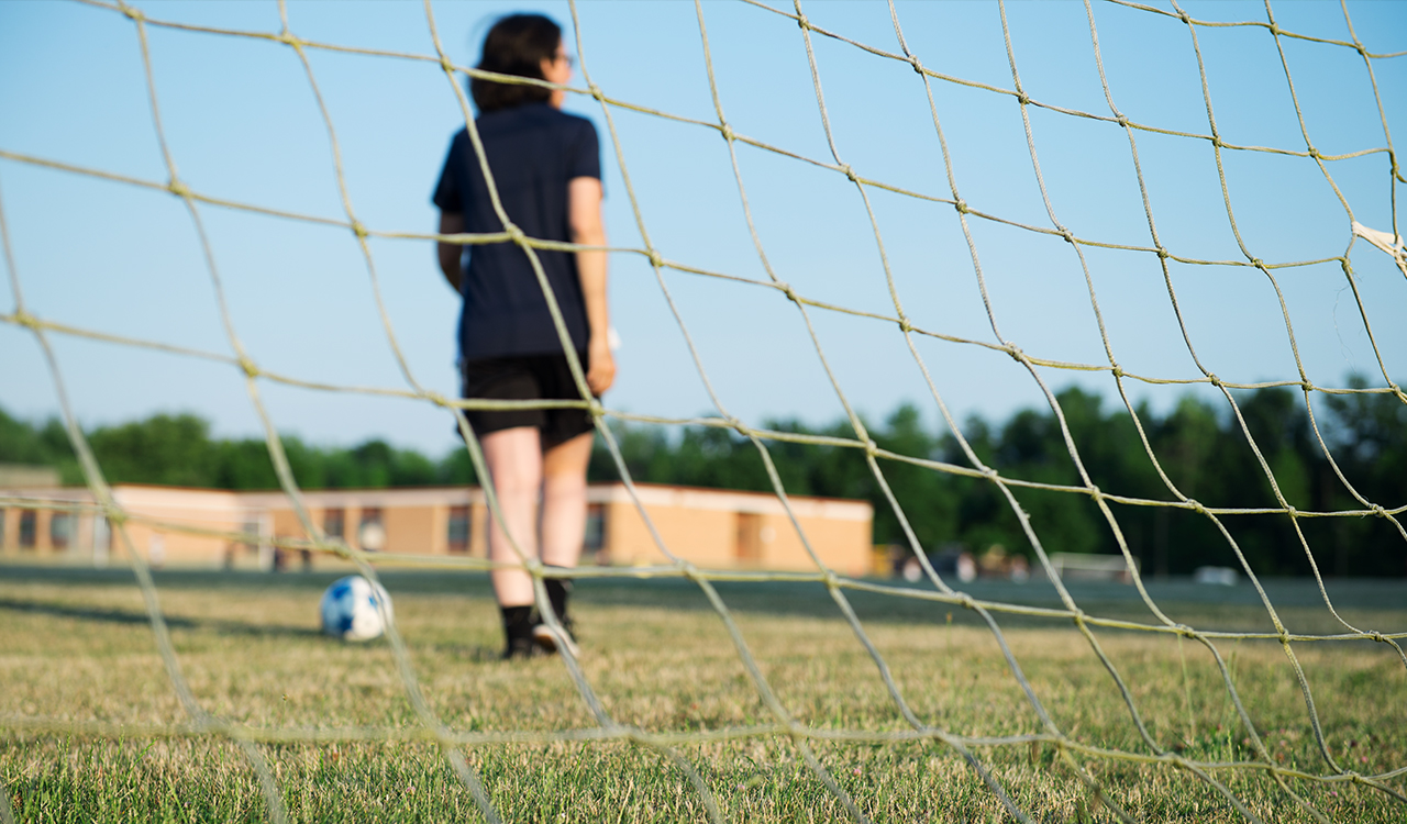 A woman in front of a soccer net