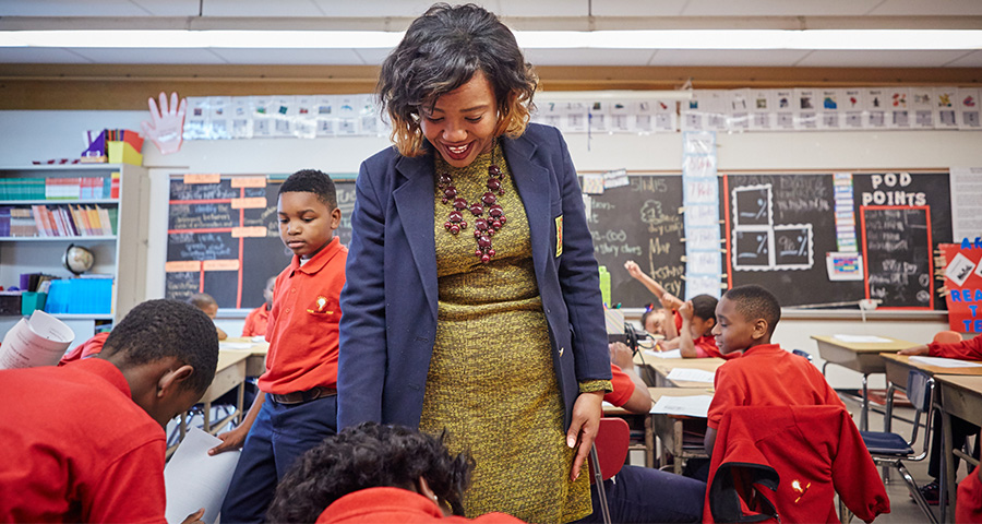A young African-American woman working with young students in her classroom.
