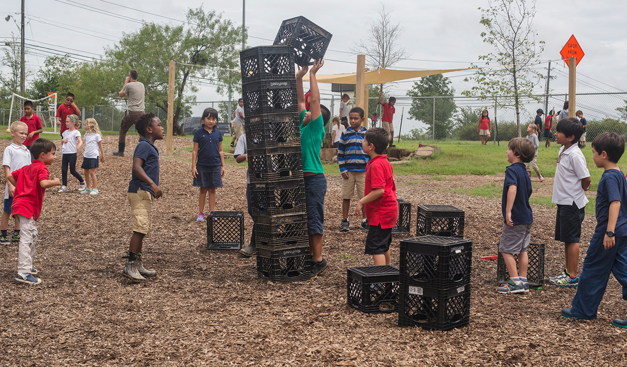 Students stacking milk crates at recess
