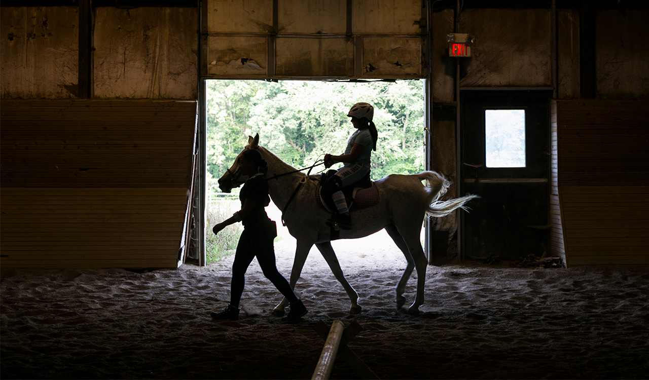 A camp instructor leads a student camper riding a horse.
