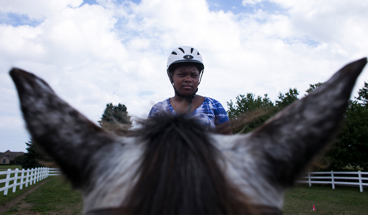 Young girl looks out into the distance while riding.