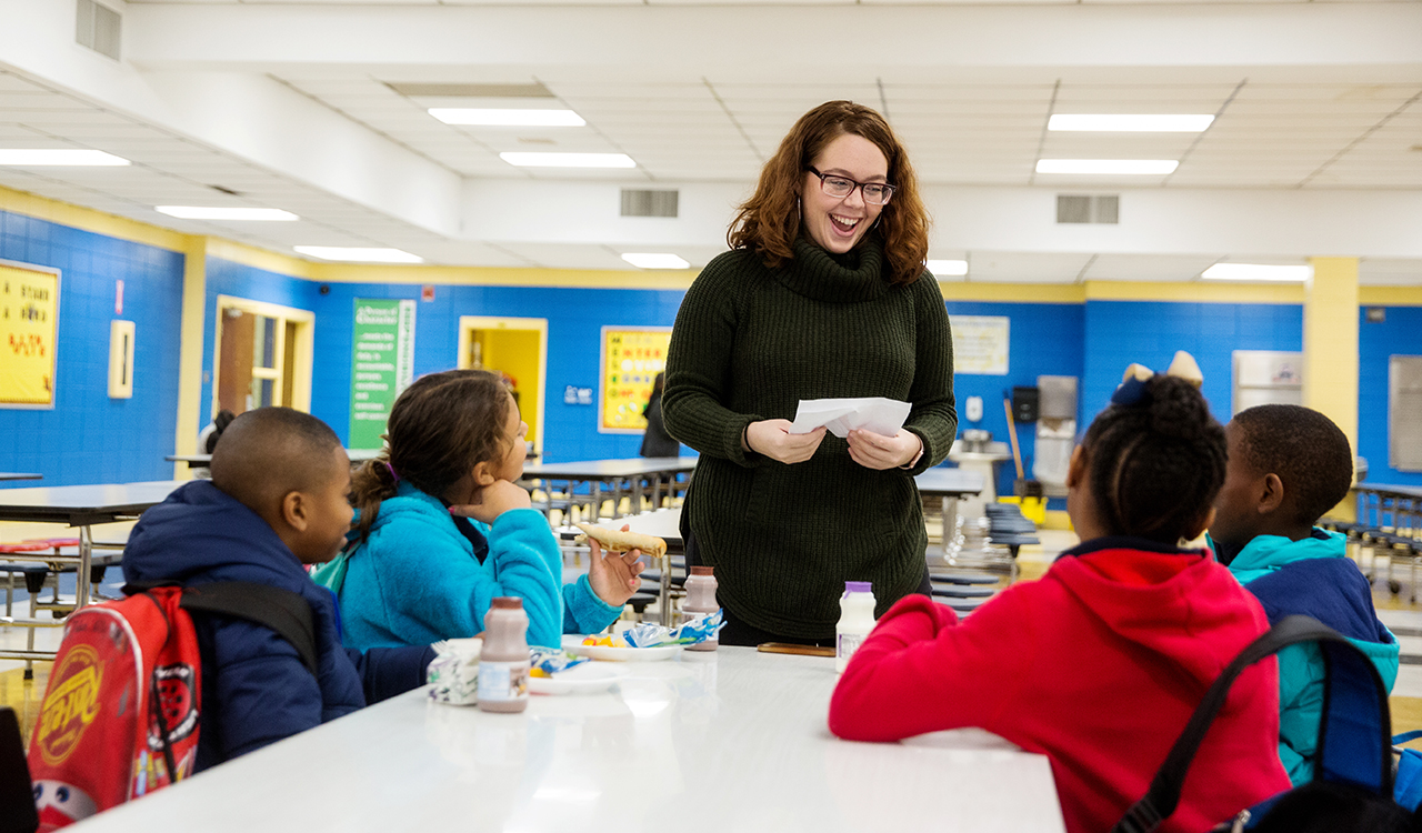 A teacher in a cafeteria with students