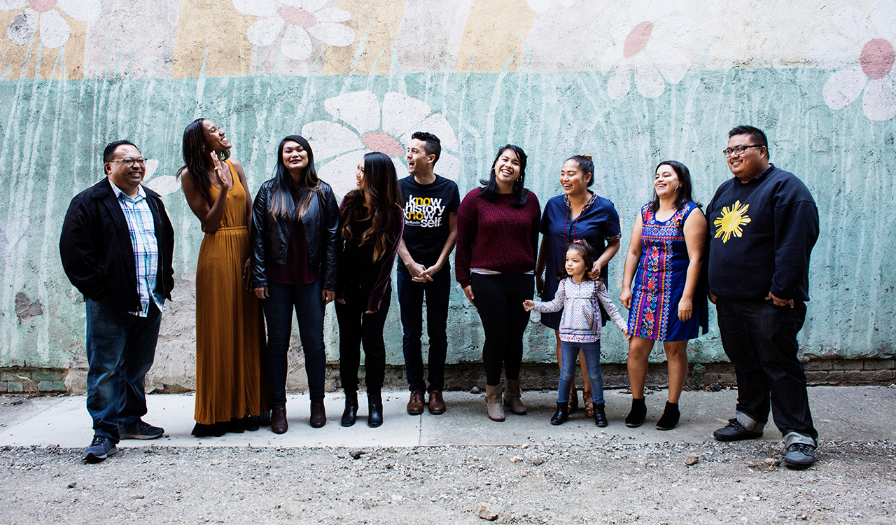 A group of people standing in front of a mural in Stockton, California.