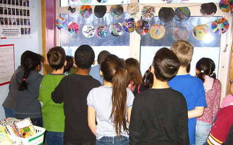 A class of middle-school students all looking through a window, with circular pieces of art strung from the ceiling above them.
