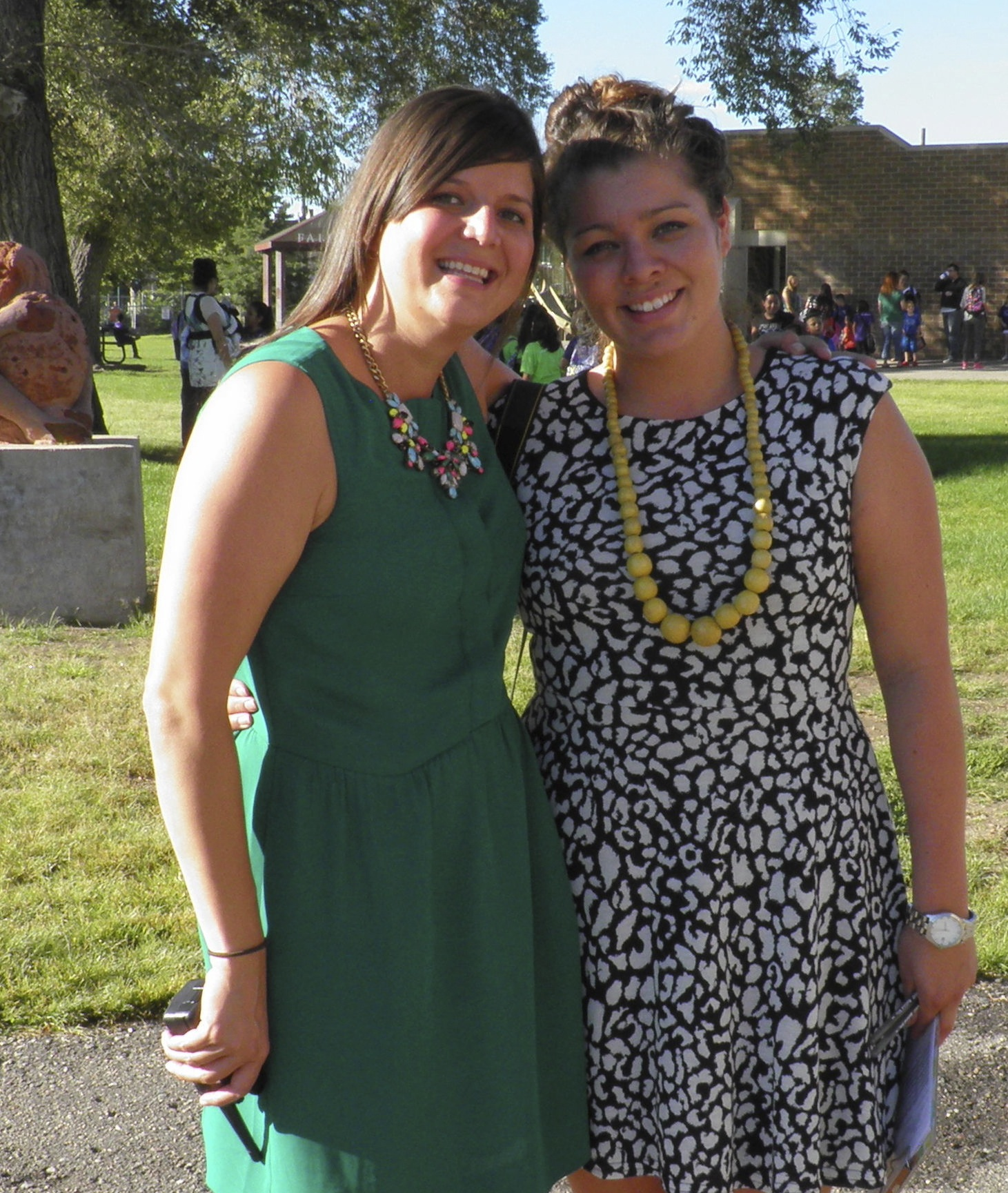 A young woman in a green dress and a young woman in a blue dress smiling in a park with their arms around each other.