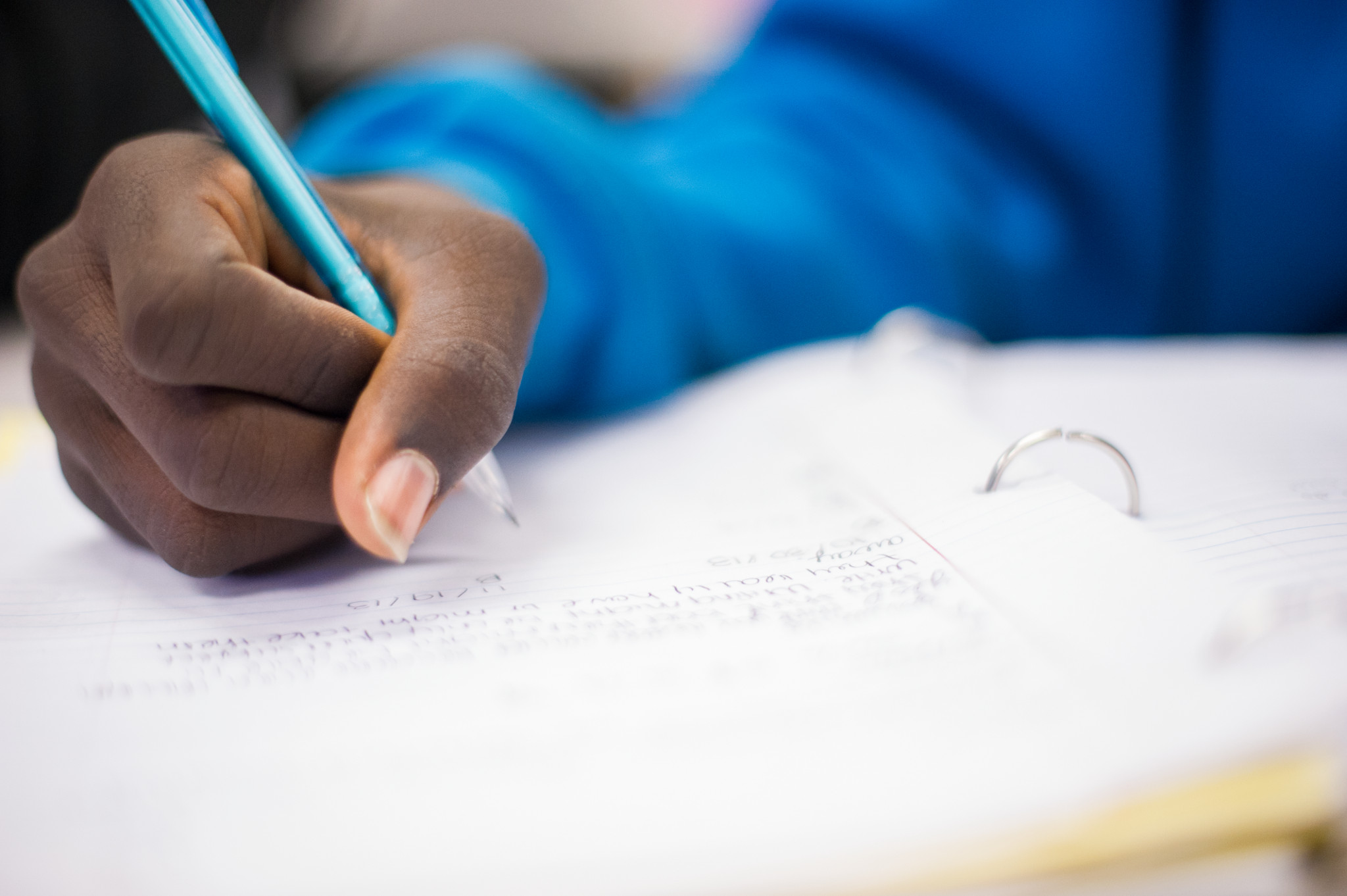 A close shot of a young girl's blue-sleeved arm and hand holding a blue pen working on a writing assignment.