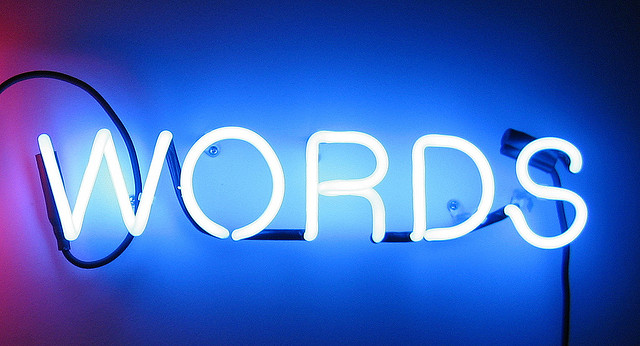 "A blue wall with a neon sign reading ""words."""